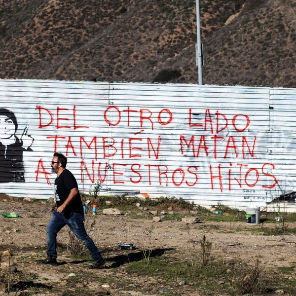 "TOPSHOT - Venezuelan artist Manuel Oliver, father of slain Joaquin Oliver, walks near his mural on the U.S.-Mexico border fence reading, ""On the other side they also kill our sons,"" in Tijuana, Baja California State, Mexico, on Dec. 19, 2018. (Credit: GUILLERMO ARIAS/AFP/Getty Images)"