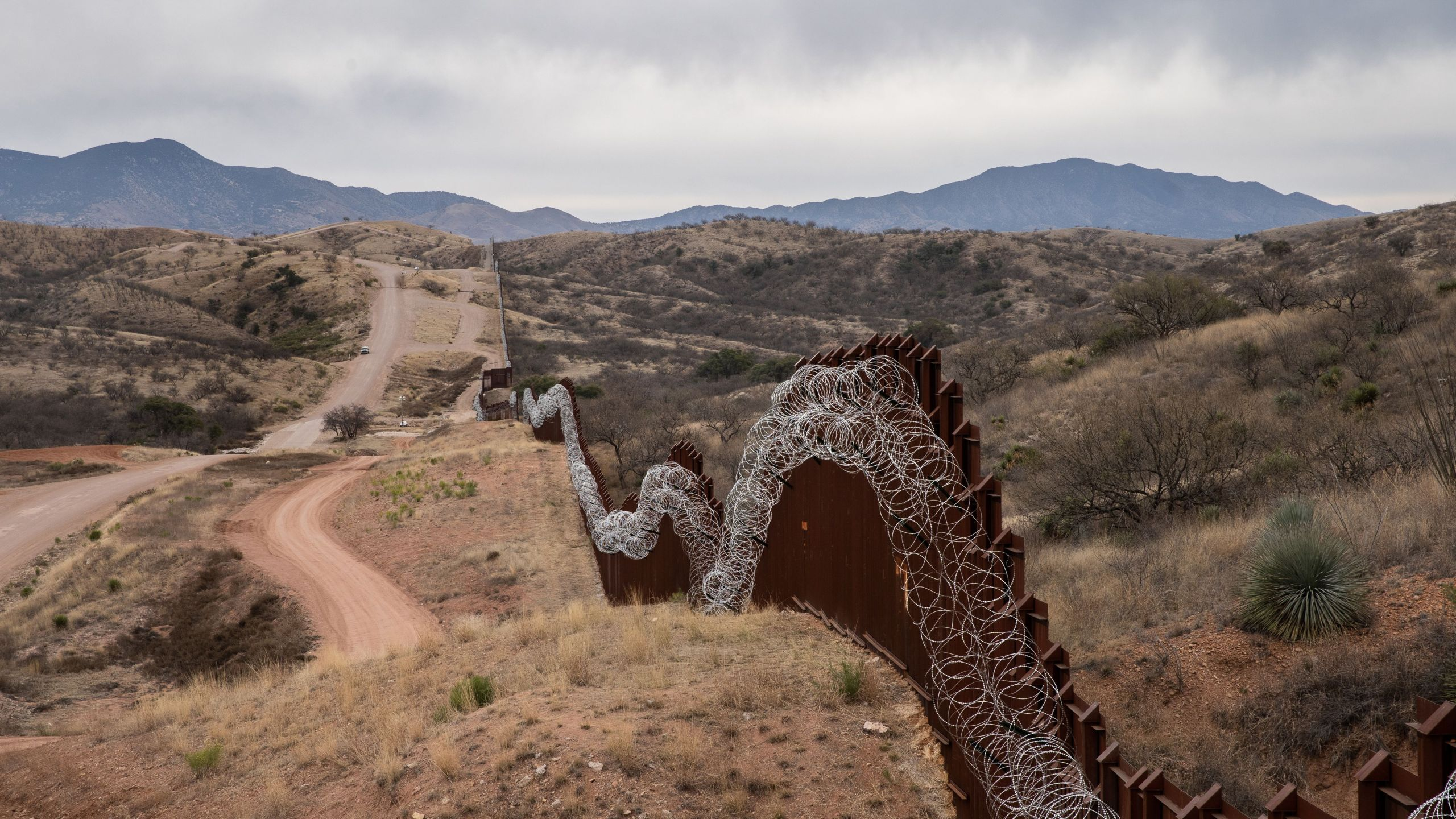 A general view of the US border fence, covered in concertina wire, separating the US and Mexico, at the outskirts of Nogales, Arizona, on February 9, 2019. (Credit: ARIANA DREHSLER/AFP/Getty Images)