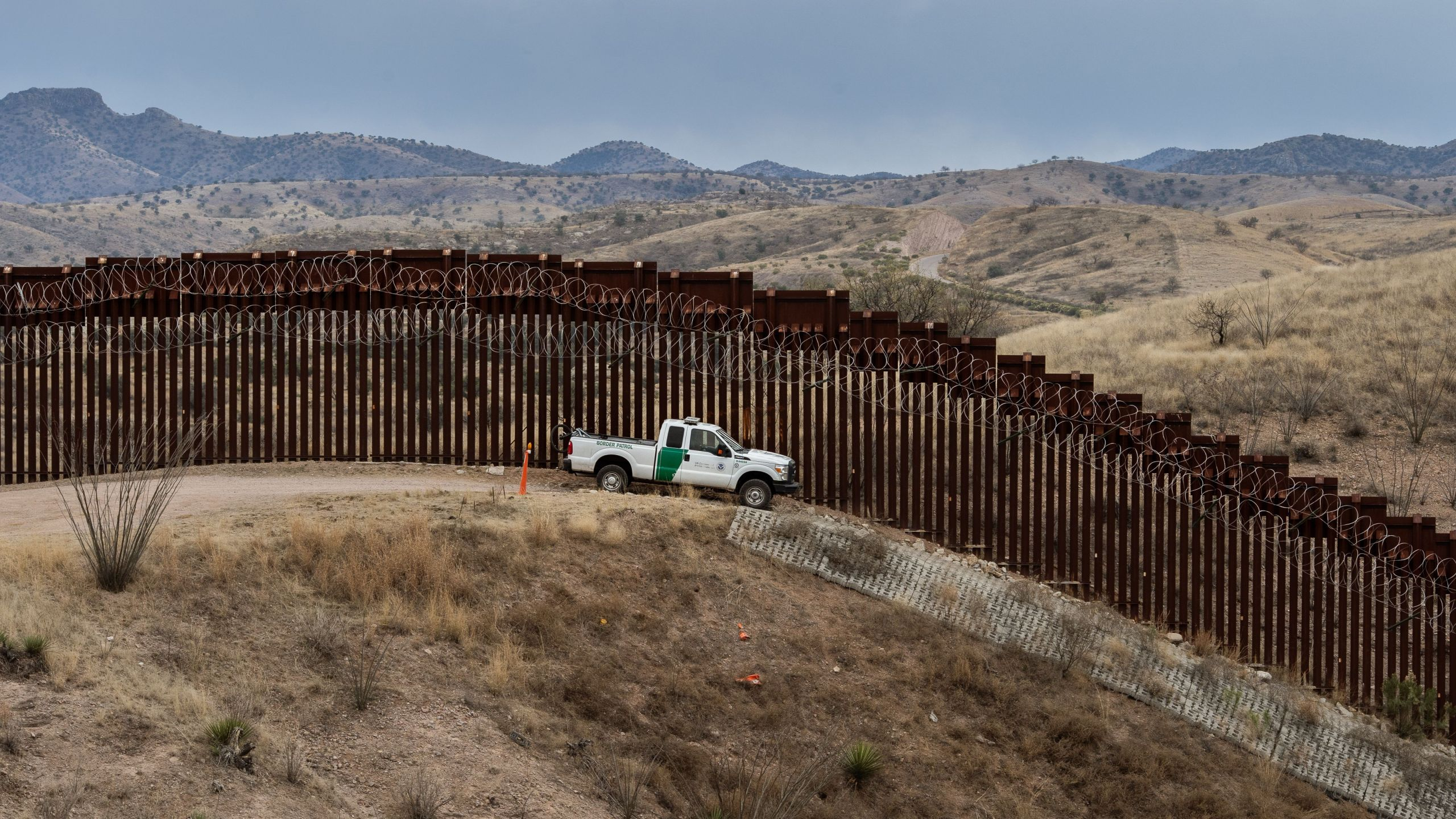 A Border Patrol officer sits inside his vehicle at the US/Mexico border fence, in Nogales, Arizona, on February 9, 2019. (Credit: ARIANA DREHSLER/AFP/Getty Images)