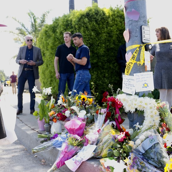 Mourners and well-wishers leave flowers at a makeshift memorial across the street from the Chabad of Poway synagogue on April 28, 2019, one day after a teenage gunman opened fire, killing one person and injuring three others including the rabbi. (Credit: Sandy Huffaker / AFP / Getty Images)