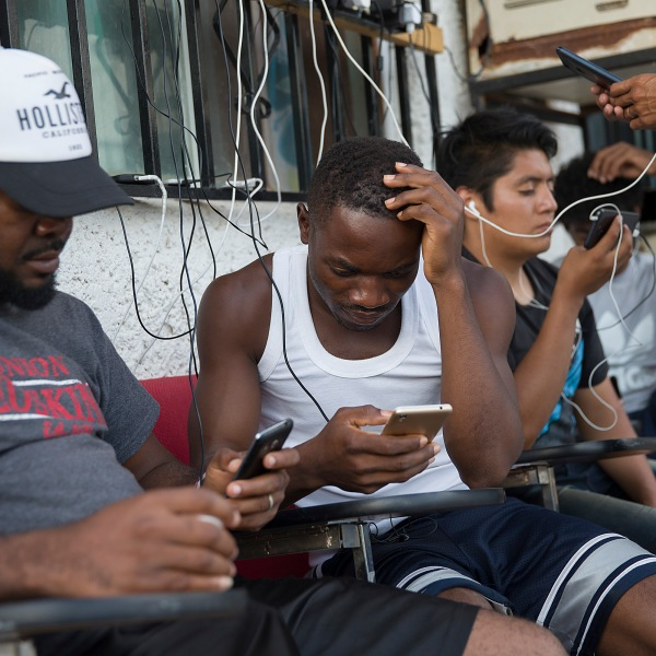 Migrants from Cameroon use their cell phones as they relax at the Albergue Para Migrantes El Buen Samaritano while waiting to have their number on a waiting list that is months long to be called to have an initial interview with a U.S. asylum officer on June 5, 2019, in Ciudad Juarez, Mexico. (Credit: Joe Raedle/Getty Images)