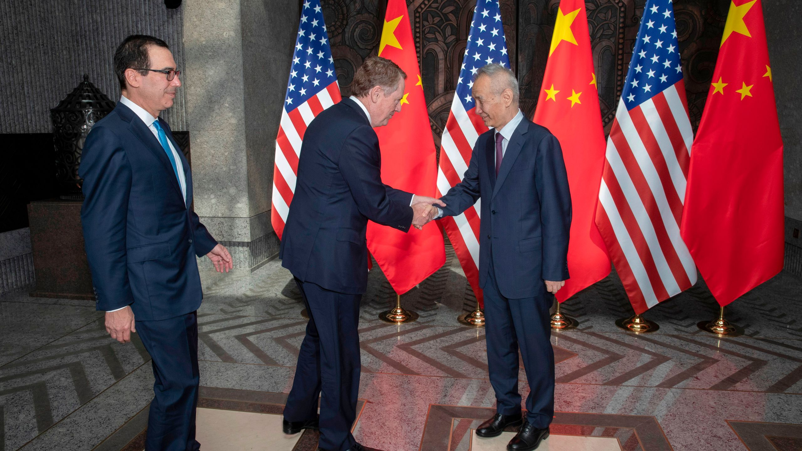 Chinese Vice Premier Liu He (right) welcomes United States Trade Representative Robert Lighthizer (center) and Treasury Secretary Steven Mnuchin (left) before holding talks at the Xijiao Conference Centre in Shanghai on July 31, 2019. (Credit: NG HAN GUAN/AFP/Getty Images)