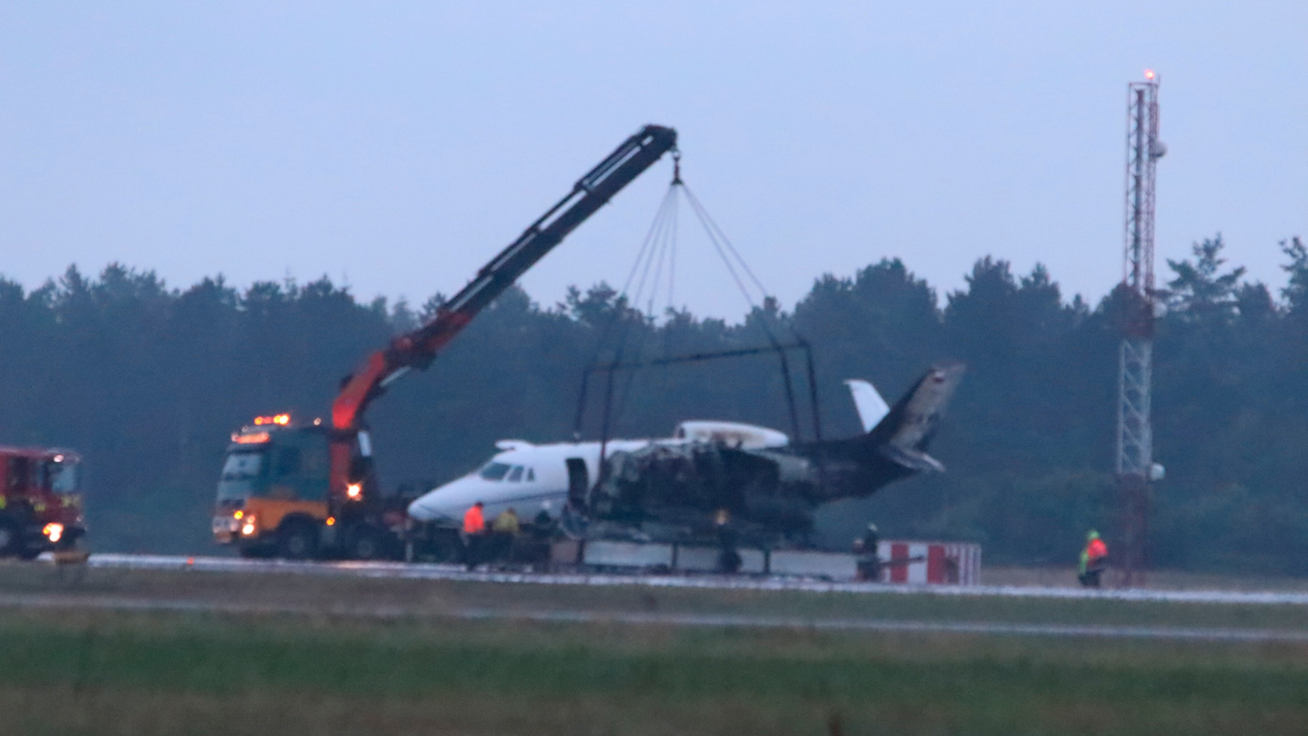 Emergency services are seen next to a Cessna 560XL that caught fire upon landing at Aarhus Airport in Tirstrup in the early hours of Aug. 6, 2019. (Credit: OEXENHOLT FOTO/AFP/Getty Images)