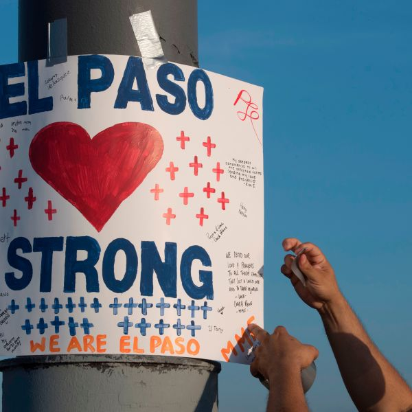 A man installs a 'El Paso Strong' sign at the makeshift memorial for victims of the shooting that left a total of 22 people dead at the Cielo Vista Mall Walmart in El Paso, Texas, on August 6, 2019. (Credit: MARK RALSTON/AFP/Getty Images)