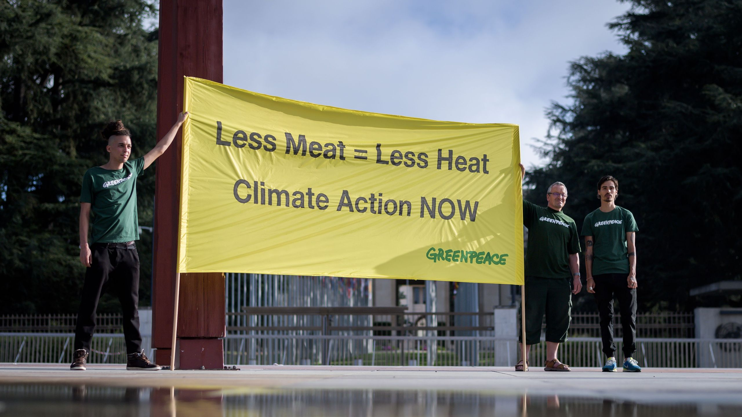 Greenpeace activists hold a banner during a protest prior to the publication by The UN's Intergovernmental Panel on Climate Change (IPCC) of a special report on climate change and land on Aug. 8, 2019, in Geneva. (Credit: FABRICE COFFRINI/AFP/Getty Images)
