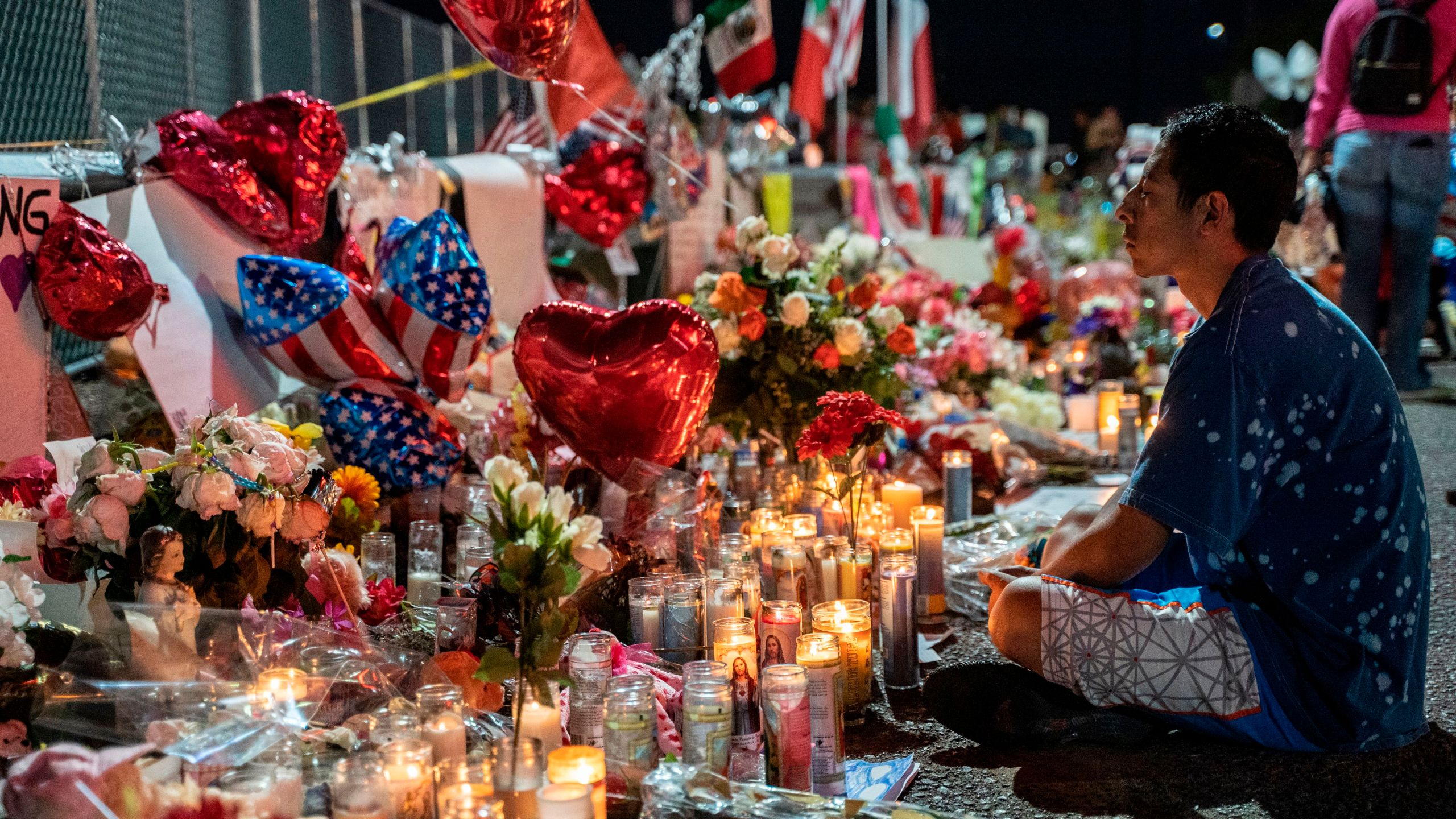 Abel Valenzuela, an El Paso local, meditates in front of the makeshift memorial for shooting victims at the Cielo Vista Mall Walmart in El Paso, Texas, on Aug. 8, 2019. (Credit: Paul Ratje / AFP / Getty Images)