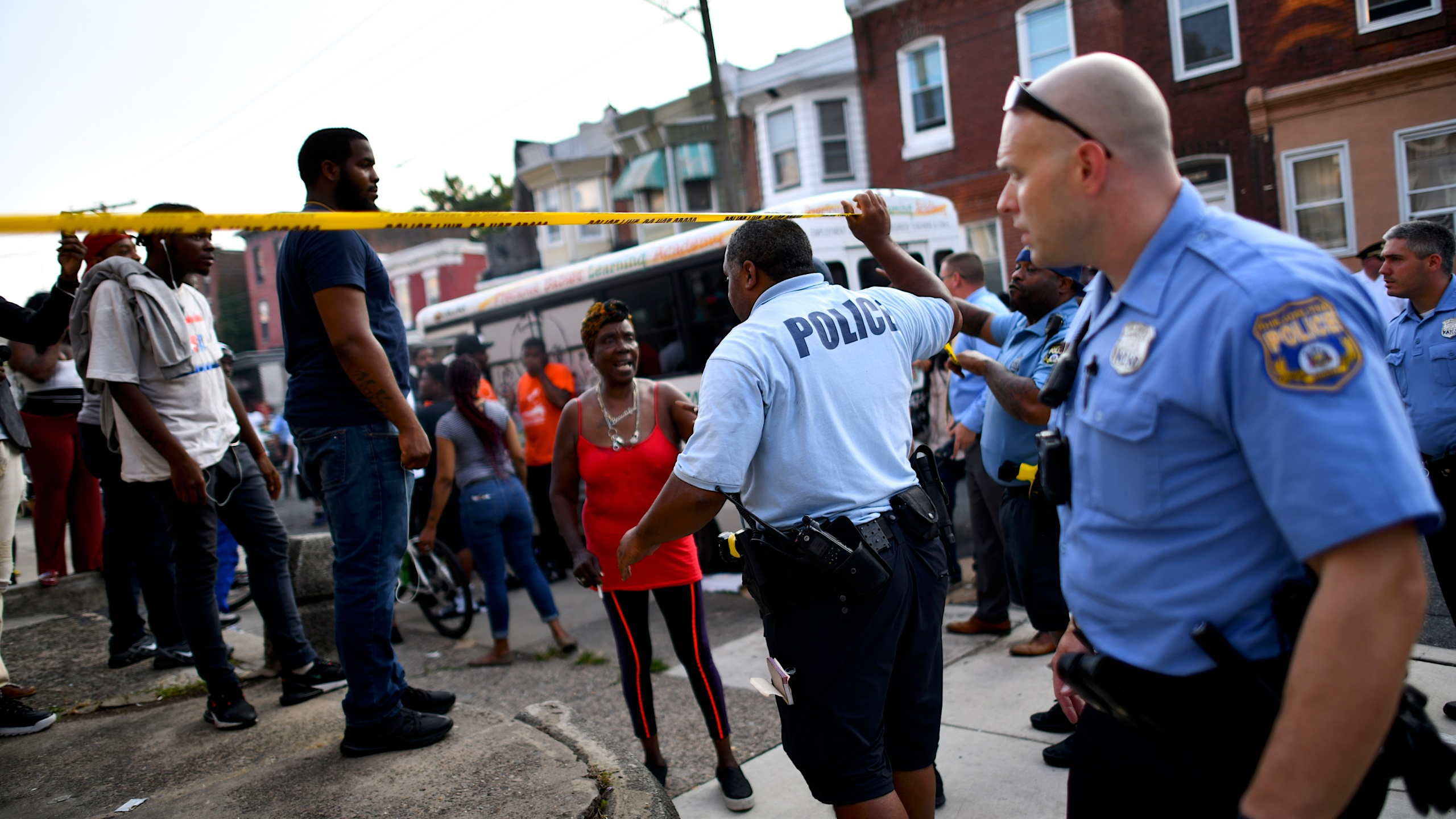 Police officers direct citizens to move back near the scene of a shooting in Philadelphia on Aug. 14, 2019. (Credit: Mark Makela / Getty Images)
