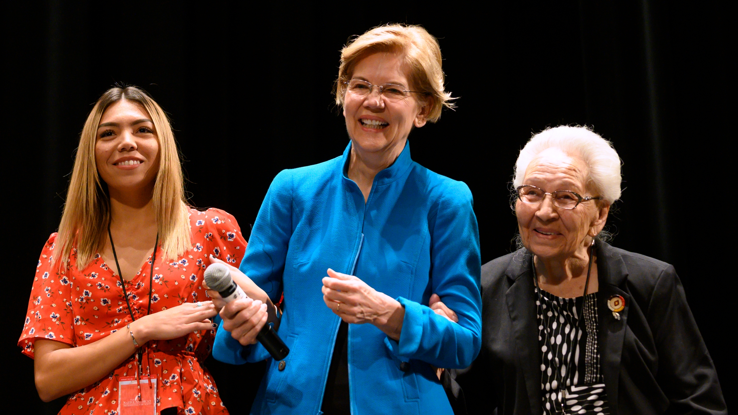 Democratic presidential candidate Sen. Elizabeth Warren (D-MA) is escorted on stage by Donna Brandis (L) and Marcella LeBeau (R) at the Frank LaMere Native American Presidential Forum on August 19, 2019 in Sioux City, Iowa. (Credit: by Stephen Maturen/Getty Images)