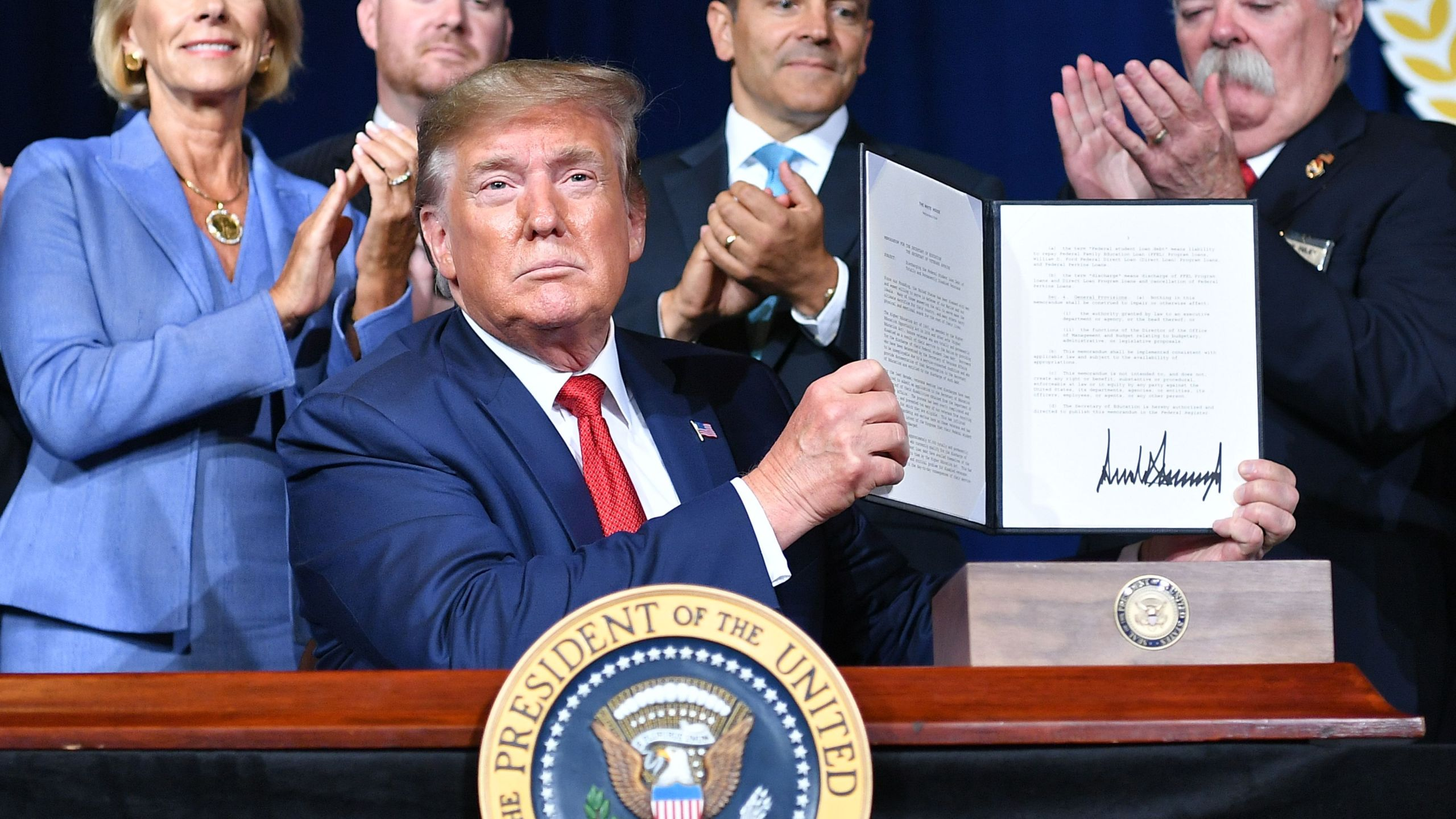 U.S. President Donald Trump signs a Presidential Memorandum on Discharging the Federal Student Loan Debt of Totally and Permanently Disabled Veterans, at the American Veterans (AMVETS) 75th National Convention in Louisville, Kentucky, on Aug. 21, 2019.(Credit: MANDEL NGAN/AFP/Getty Images)