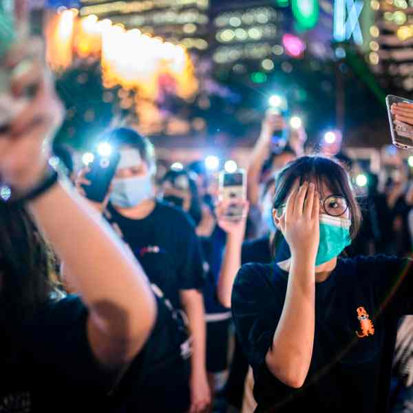 Secondary school students cover their right eye as they hold up their phone torches while attending a rally at Edinburgh Place in Hong Kong on Aug. 22, 2019. (Credit: ANTHONY WALLACE/AFP/Getty Images)