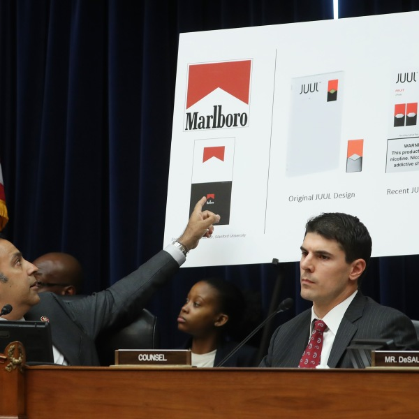 Chairman Raja Krishnamoorthi, left, points to a poster showing similarities between Marlboro cigarette ads and Juul vaping paraphernalia during a House Economic and Consumer Policy Subcommittee hearing on July 25, 2019. (Credit: Mark Wilson / Getty Images)