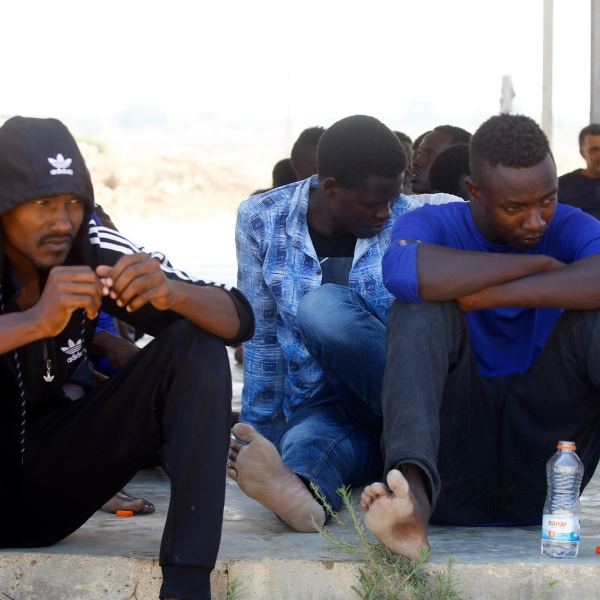 Rescued migrants sit in a coast guard point in Khoms, some 60 miles from the Libyan capital of Tripoli, on Aug. 27, 2019, after they were saved off the coast of the Libyan city. (Credit: MAHMUD TURKIA/AFP/Getty Images)