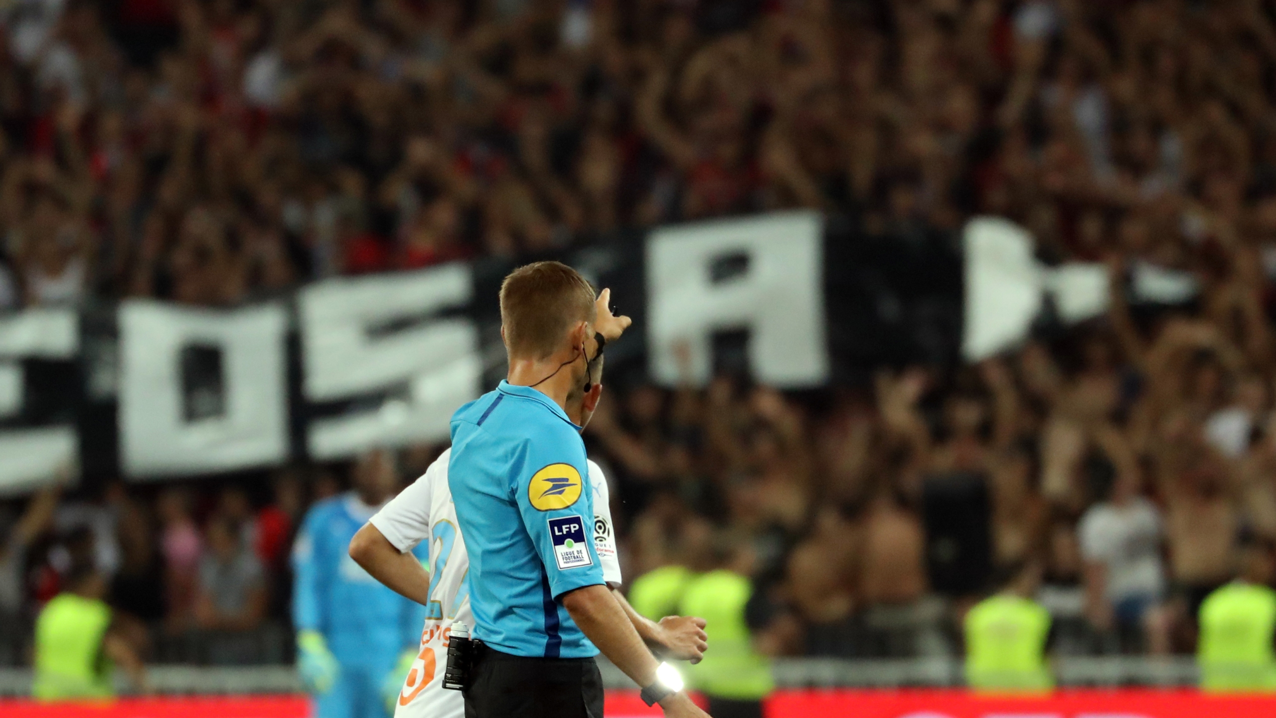 French referee Clement Turpin gestures as he halts the game after supporters shouted homophobic songs and brandished banners during the football match between OGC Nice and Olympique de Marseille on August 28, 2019 in southeastern France. (Credit: VALERY HACHE/AFP/Getty Images)