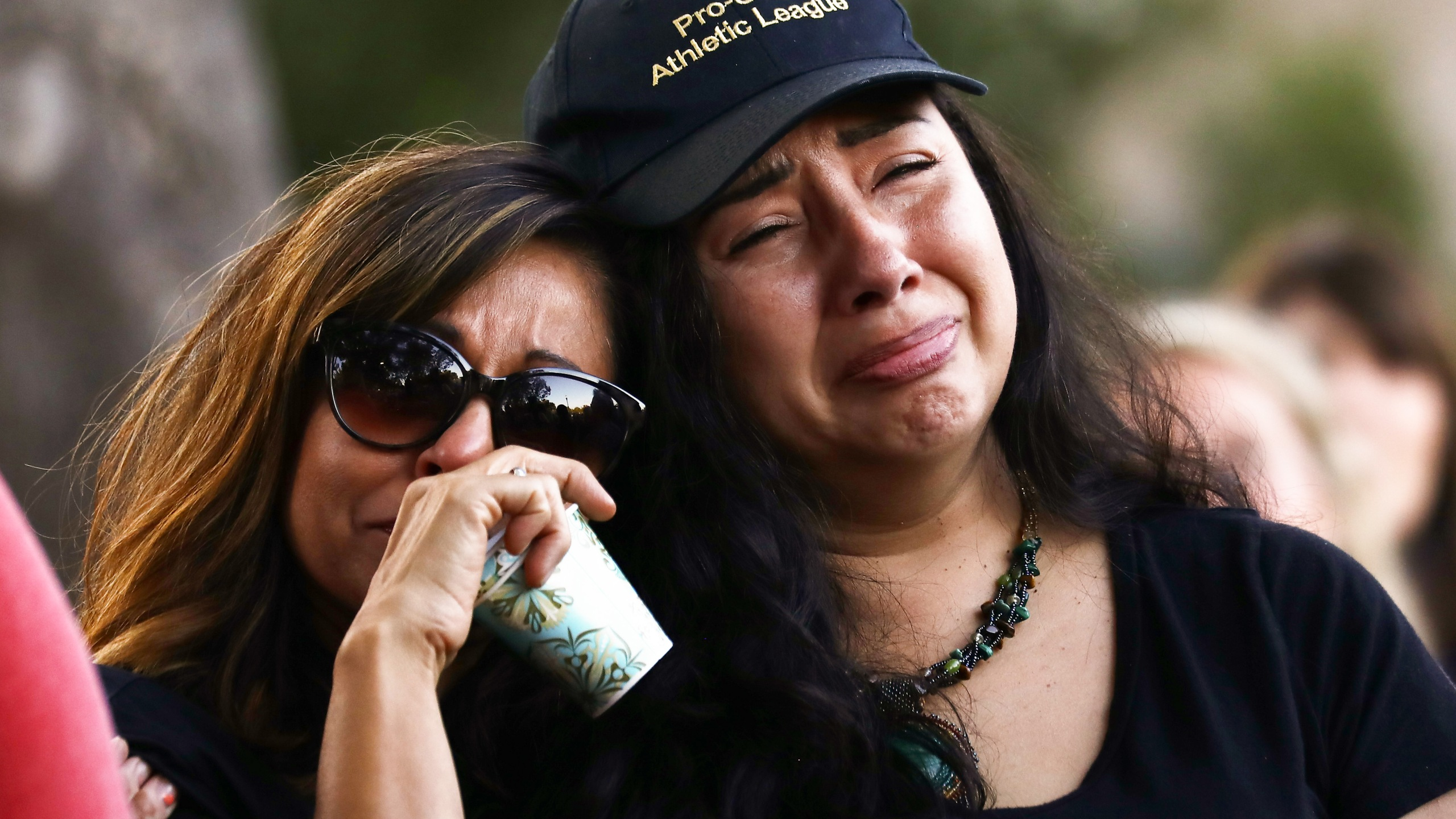 People embrace at a vigil for victims of the mass shooting at the Gilroy Garlic Festival on July 29, 2019 in Gilroy. (Credit: Mario Tama/Getty Images)