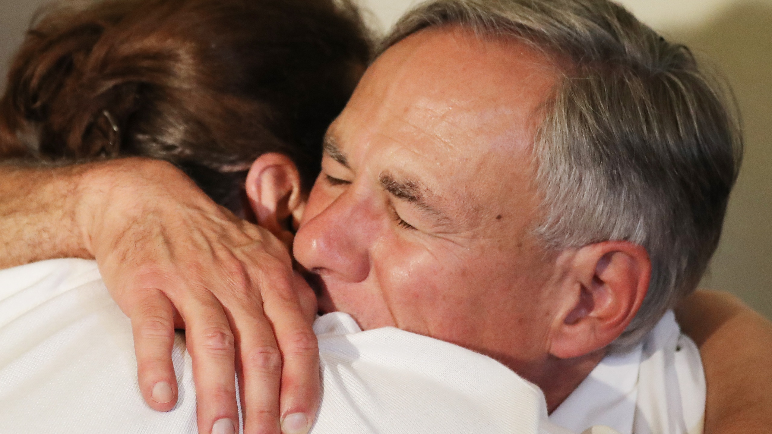 Texas Governor Greg Abbott (right) hugs a woman following a vigil for victims at St. Pius X Church after a mass shooting which left at least 20 people dead on August 3, 2019, in El Paso, Texas. (Credit: Mario Tama/Getty Images)
