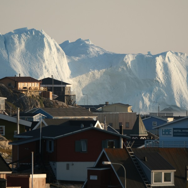 Icebergs in the Ilulissat Icefjord loom behind buildings on Aug. 4, 2019 in Ilulissat, Greenland. (Credit: Sean Gallup/Getty Images)