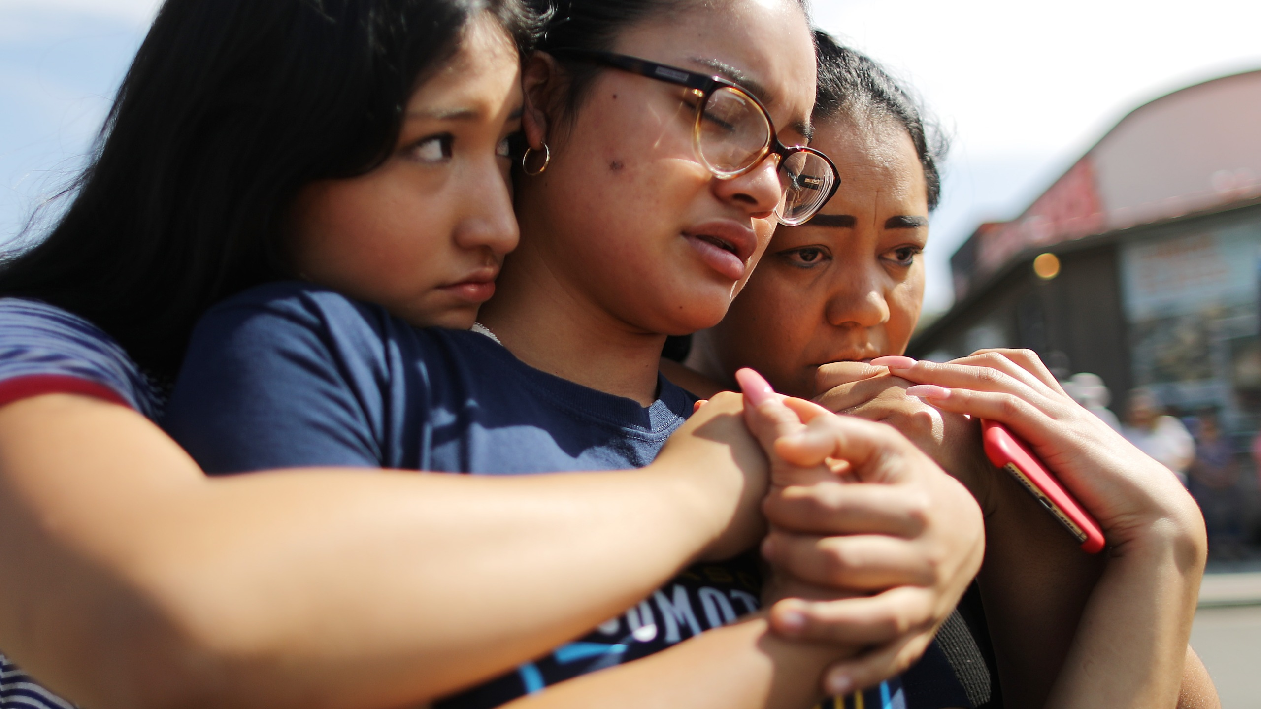 Mother Aidee Gutierrez, right, originally from Mexico, and daughters Marlene Gutierrez and Brissa Martinez embrace at a makeshift memorial outside Walmart in El Paso, near the scene of a mass shooting that days before left at least 22 people dead, on Aug. 5, 2019. (Credit: Mario Tama / Getty Images)