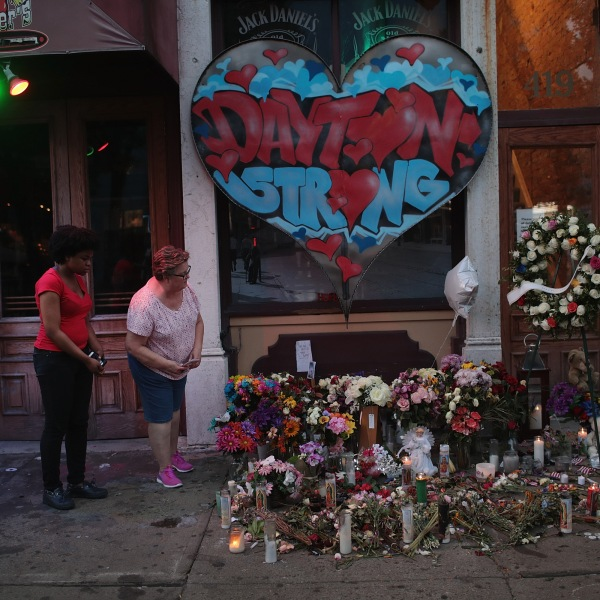 People look over a memorial to those killed in a mass shooting while the businesses along E. 5th Street in the Oregon District try to return to normal on Aug. 6, 2019, in Dayton, Ohio. (Credit: Scott Olson/ Getty Images)