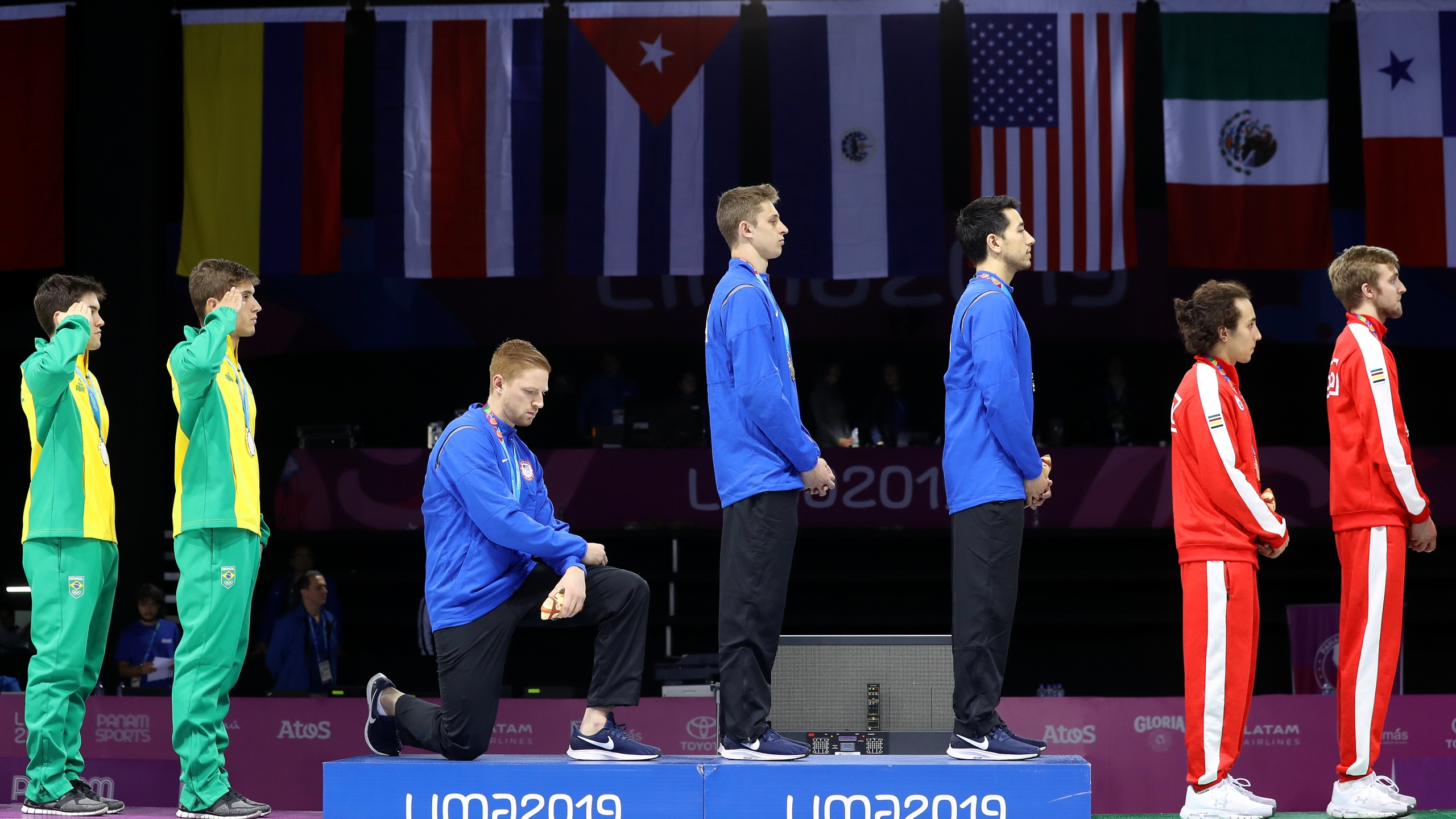 Gold medalist Race Imboden takes a knee during the national anthem ceremony in the 2019 Pan American Games at Fencing Pavilion of Lima Convention Center on Aug. 9, 2019 in Peru. (Credit: Leonardo Fernandez/Getty Images)
