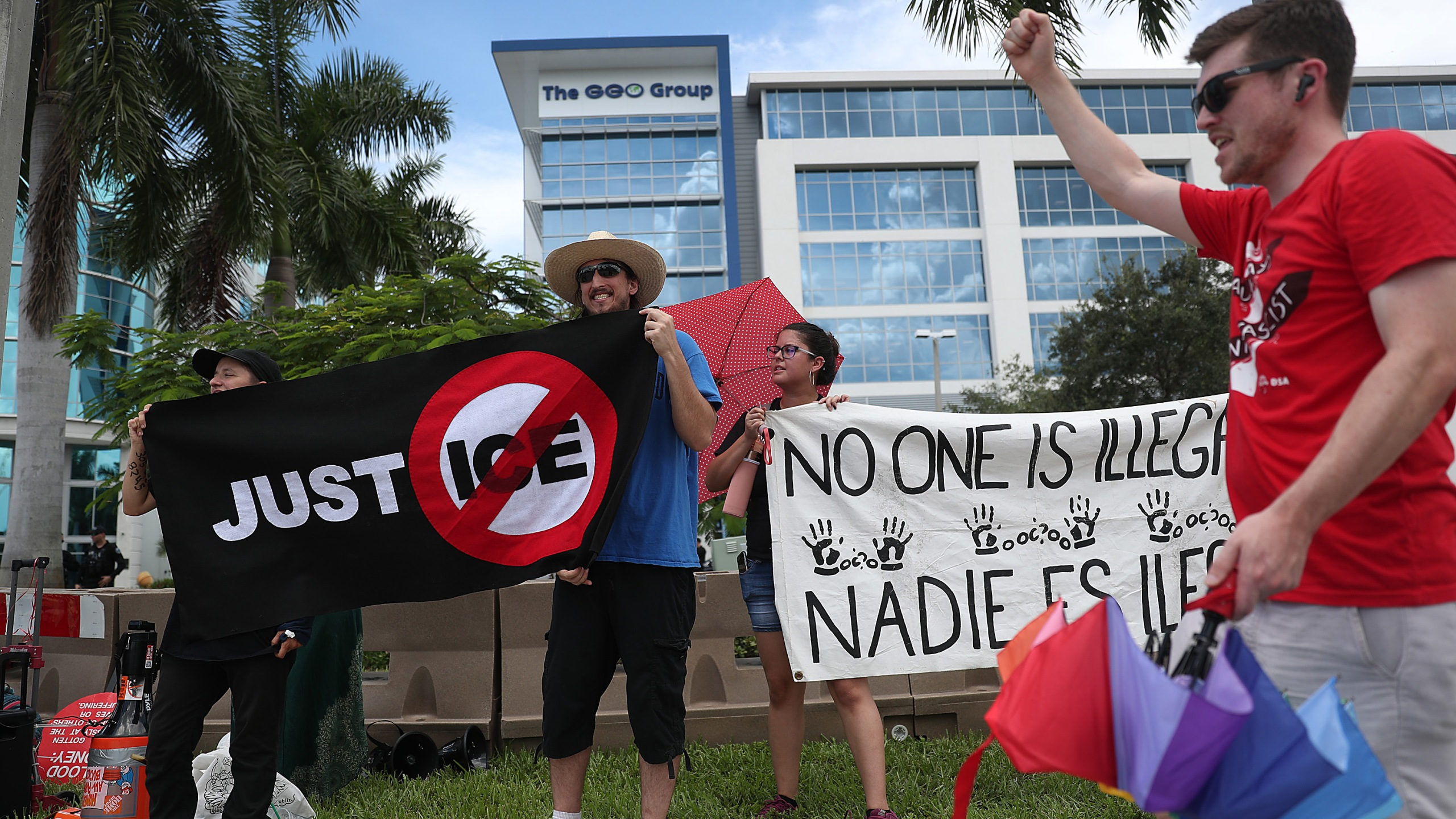 Activists and protesters including the group Never Again Action are seen as they protest outside the headquarters of the private prison company Geo Group on Aug. 12, 2019, in Boca Raton, Fla. (Credit: Joe Raedle/Getty Images)