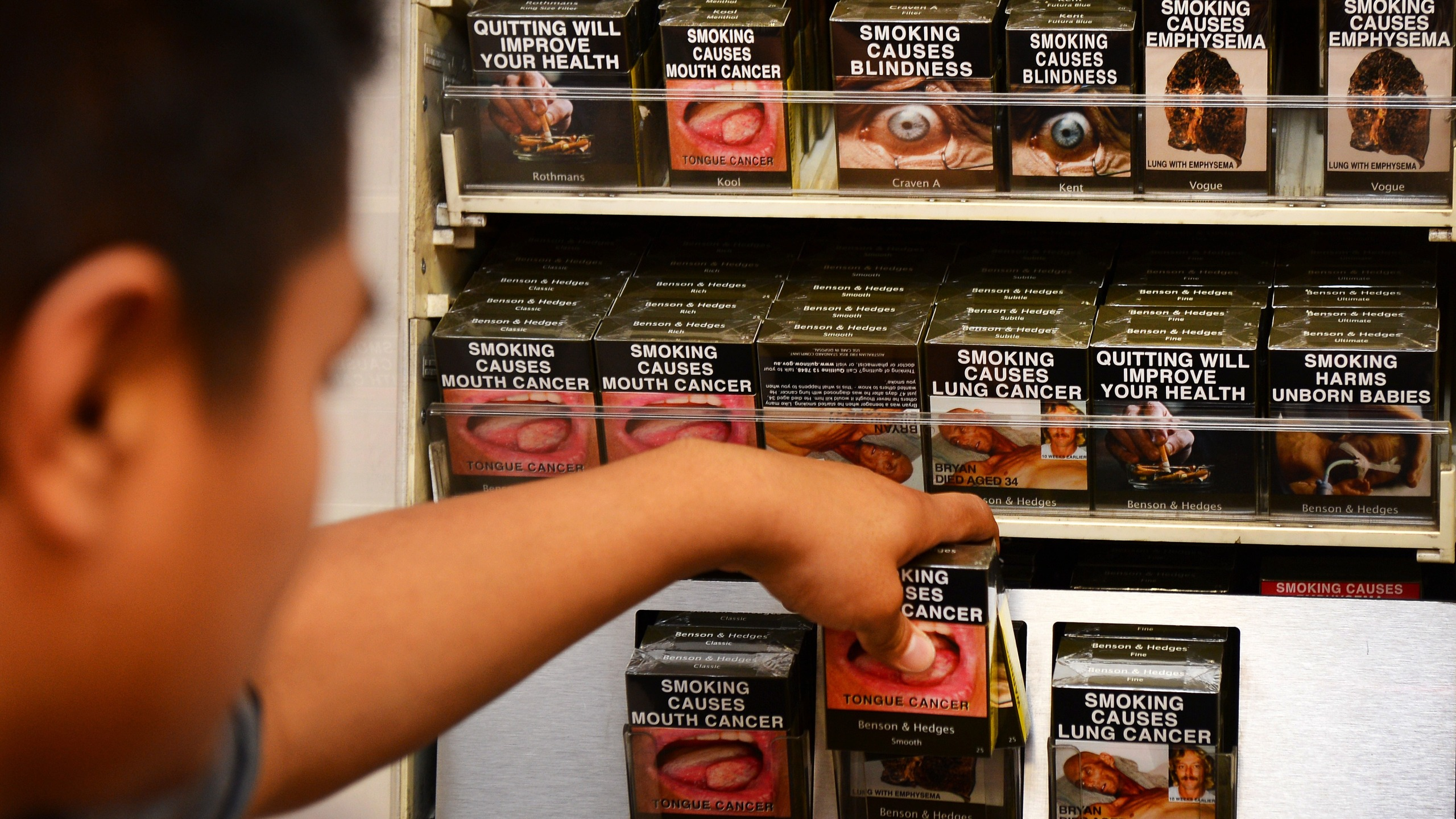 An employee in a bookshop adjusts packaged cigarettes which have to be sold in identical olive-brown packets bearing the same typeface and largely covered with graphic health warnings, with the same style of writing so the only identifier of a brand will be the name on the packet, in Sydney on Dec. 1, 2012. (Credit: WILLIAM WEST/AFP/Getty Images)