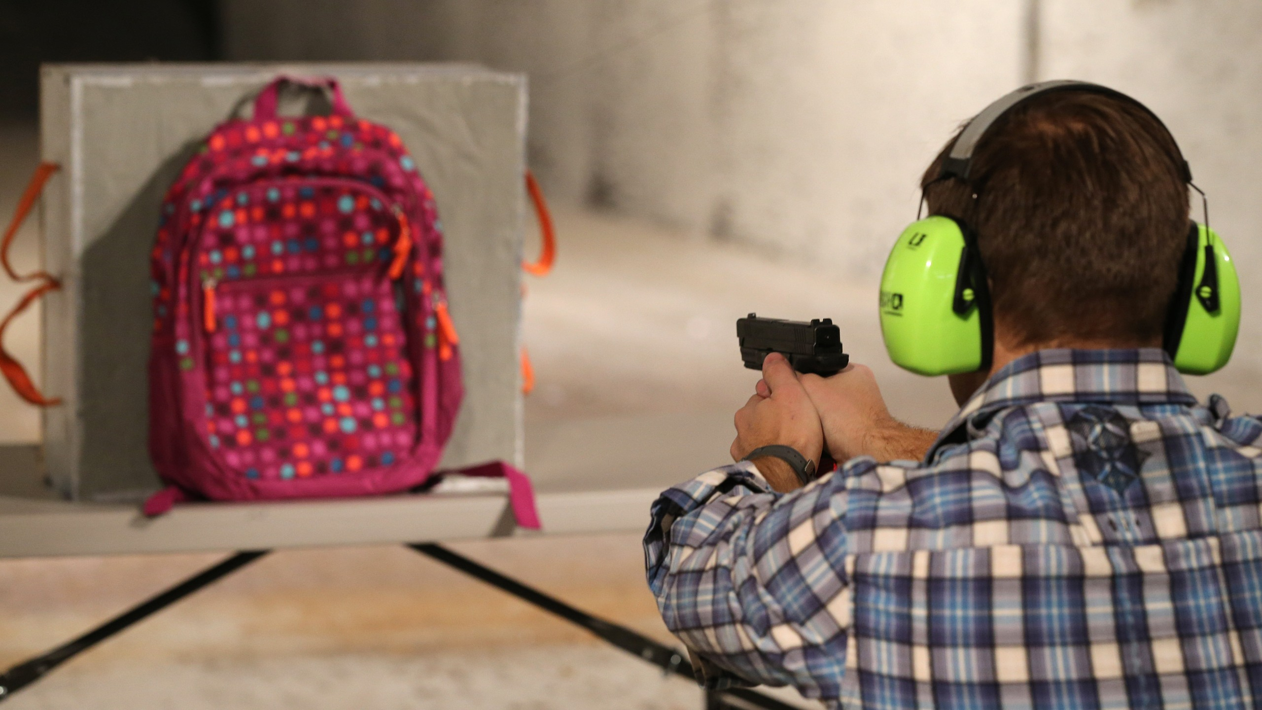 Chief Operating Officer for Amendment II, Rich Brand, shoots a child's backpack with their Rynohide CNT Shield in it on December 21, 2012 in Salt Lake City, Utah. (Credit: George Frey/Getty Images)