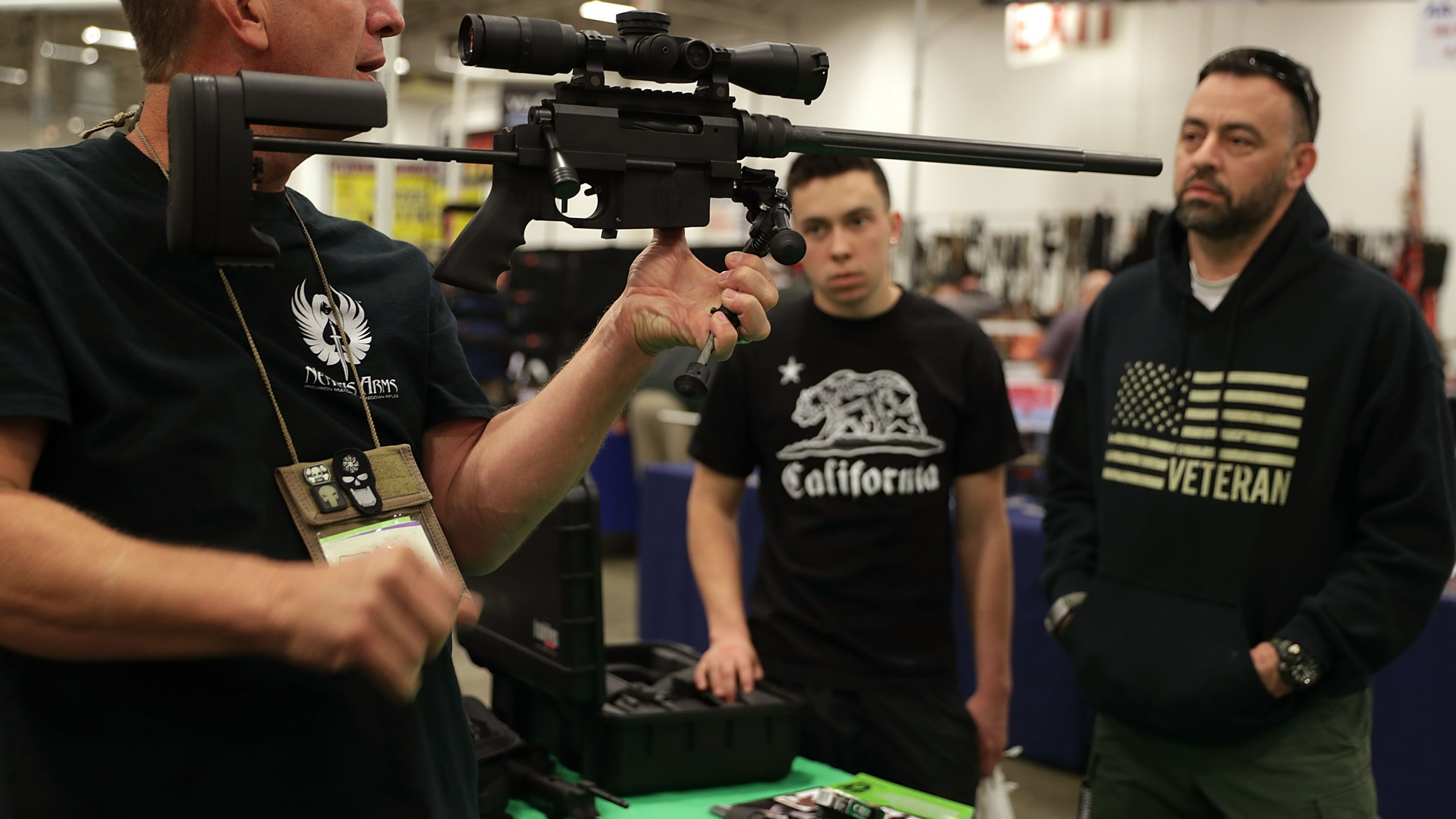 A gun seller demonstrates a firearm to potential buyers during the Nation's Gun Show on Nov. 18, 2016, at Dulles Expo Center in Chantilly, Virg. (Credit: Alex Wong/Getty Images)