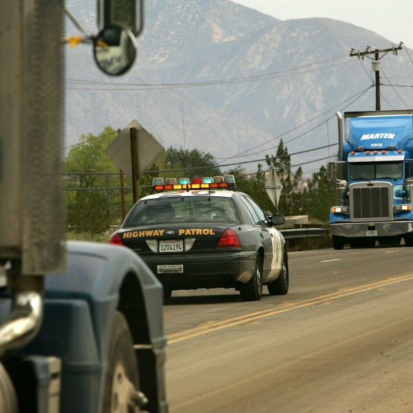 Two big rigs and a California Highway Patrol vehicle are seen on July 23, 2007 near Wrightwood. (Credit: David McNew/Getty Images)