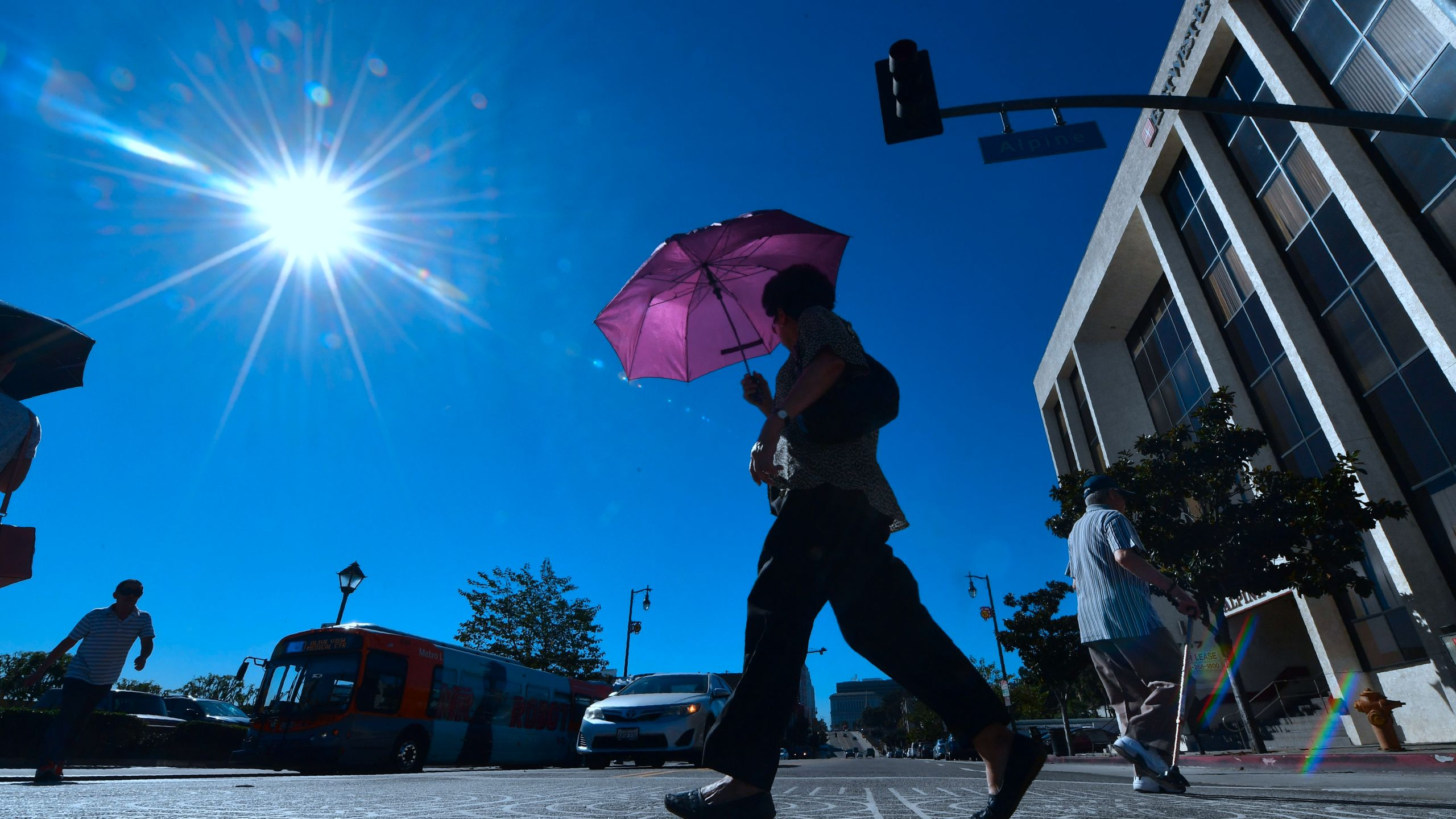 A pedestrian uses an umbrella on a hot sunny morning in Los Angeles Oct. 24, 2017, amid a late season heatwave hitting Southern California. (Credit: FREDERIC J. BROWN/AFP/Getty Images)