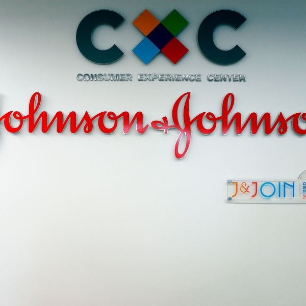 The logo of multinational medical devices and pharmaceutical company Johnson & Johnson is seen at the entrance of the research and development plant, in Val-de-Reuil, northwestern France, on Nov. 30, 2017. (Credit: CHARLY TRIBALLEAU/AFP/Getty Images)
