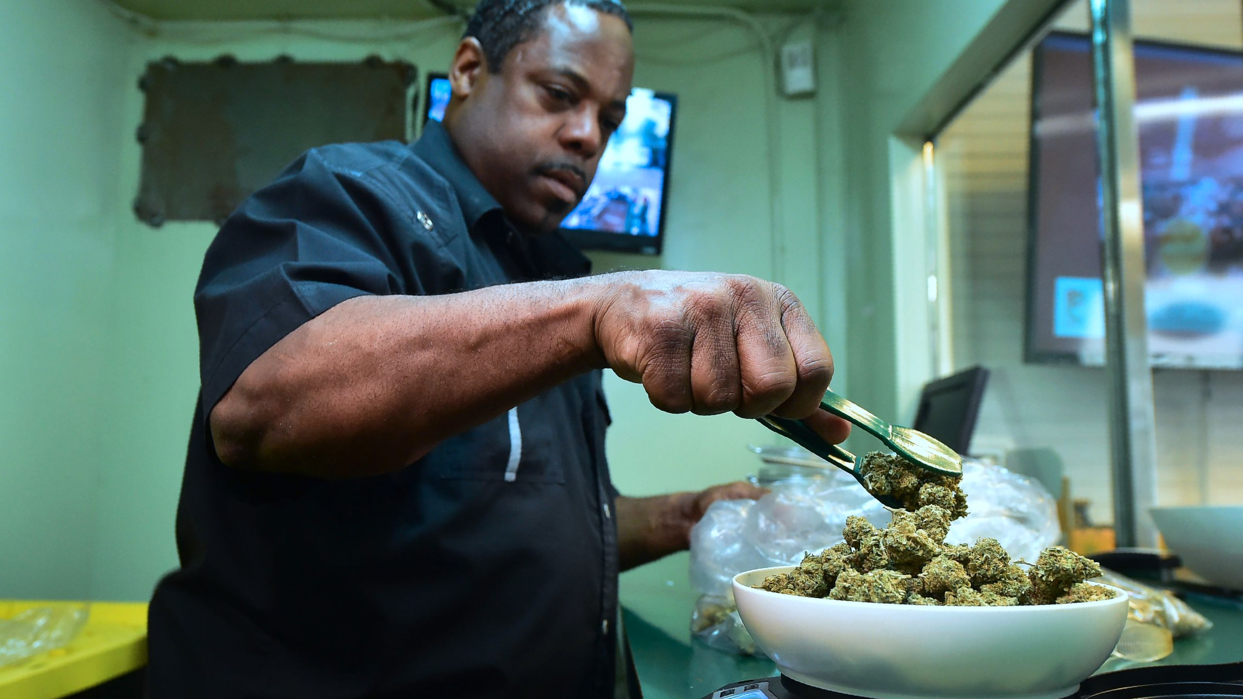 Eddie Irby weighs the marijuana at Virgil Grant's dispensary in Los Angeles, on Feb. 8, 2018. (Credit: FREDERIC J. BROWN/AFP/Getty Images)