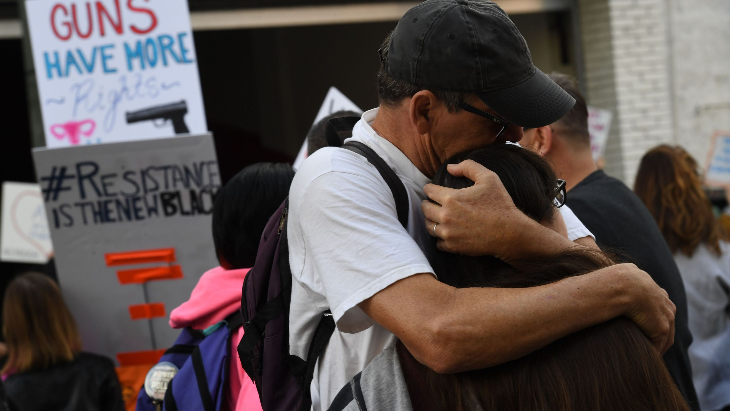 """Two people hug as crowds rally for tighter gun laws during the student-organized """"March For Our Lives"""" protest in Los Angeles on March 24, 2018. (Credit: MARK RALSTON/AFP/Getty Images)"""