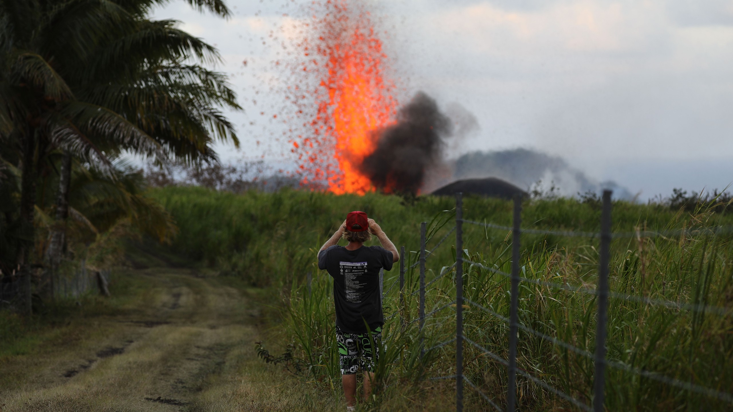 A man takes a photo of a lava fountain from a Kilauea volcano fissure on Hawaii's Big Island on May 18, 2018, in Kapoho, Hawaii. (Credit: Mario Tama/Getty Images)