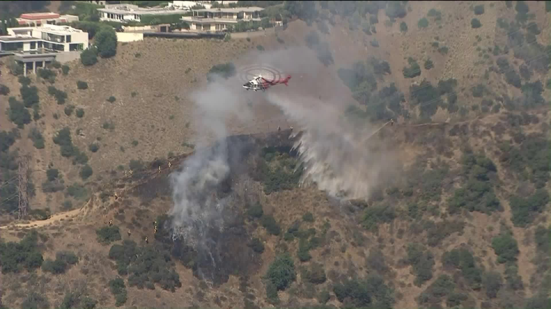 A helicopter drops water on a brush fire in Hollywood Hills West on Aug. 14, 2019. (Credit: KTLA)