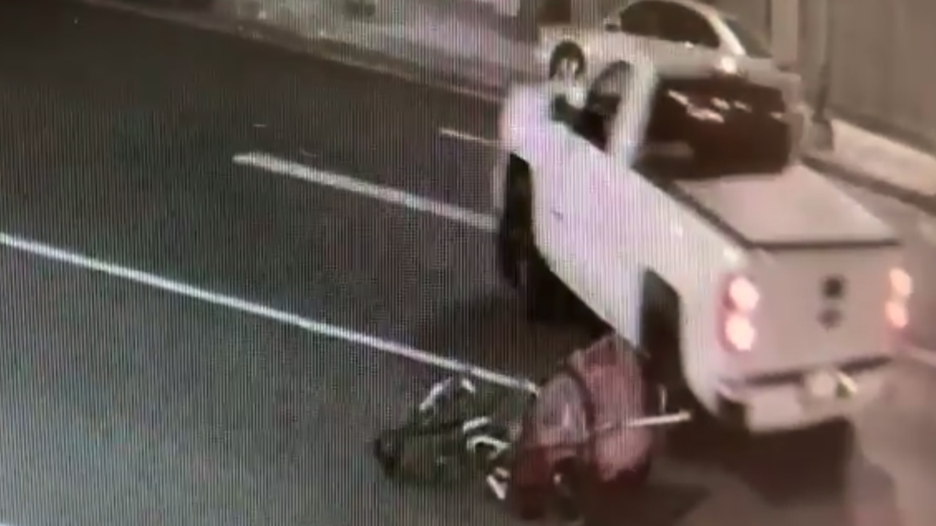 This still from surveillance video released by LAPD on Aug. 26, 2019, shows a truck flee the scene after hitting a man on a bicycle, which is seen near the truck's tire. (Credit: KTLA)