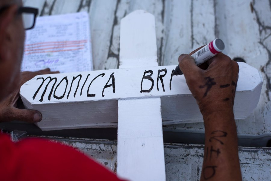 """Greg Zanis writes the name of Monica Brickhouse, a victim in the Dayton shooting, on a cross he constructed in his Aurora workshop. He says he's spoken to relatives who still have crosses he made 20 years ago. """"That's all they have left, and it means everything to them."""" (Credit: Mark Felix / CNN)"""