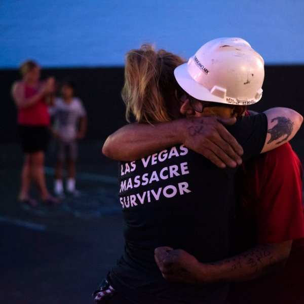 """Greg Zanis embraces Leah Matthews, 33, of Cincinnati, who, as her shirt says, survived the 2017 mass shooting at a country music festival in Las Vegas. Zanis honored those victims with 58 crosses, which he placed in front of the iconic """"Welcome to Fabulous Las Vegas"""" sign. Clark County, Nevada, officials declared November 12 """"Greg Zanis Day"""" and presented the carpenter with a key to the Las Vegas Strip. (Credit: Mark Felix / CNN)"""