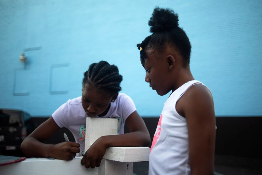 Samiya Booker, 10, writes on one of the crosses after Greg Zanis unloaded it from his truck. Her sister, Neveah, 11, looks on. Zanis leaves the crosses at the shooting sites for 40 days before returning and presenting them to family members. The number is arbitrary, he said. It just seems like the right amount of time. (Credit: Mark Felix / CNN)