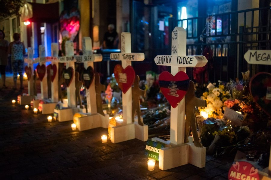 Greg Zanis writes victims' names and the cities where they were killed on each cross, along with a Bible verse. He also welcomes others to adorn them with remembrances. After he placed the crosses Wednesday on Dayton's Fifth Street, mourners put candles in front of each memorial. (Credit: Mark Felix / CNN)