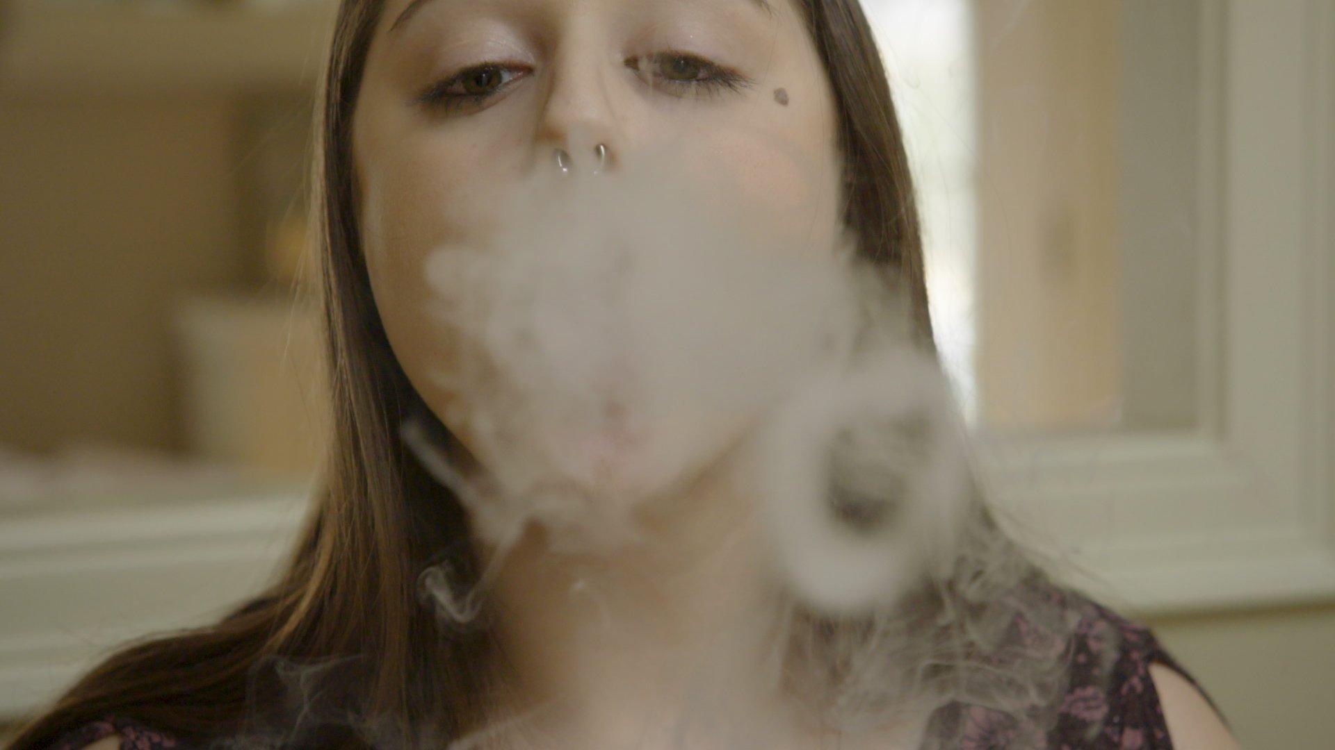 A teenage girl makes vapor circles while using an e-cigarette. (Credit: CNN)