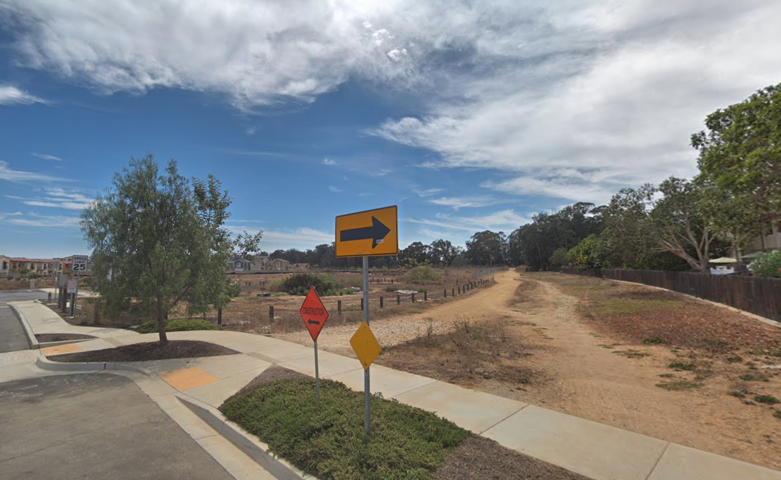 A dirt path near Phelps Road and Ocean Walk Lane is shown in a Street View image from Google Maps.