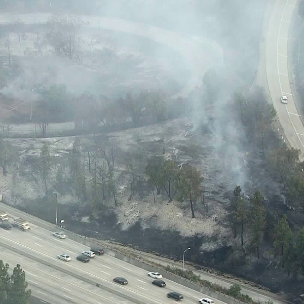 Smoke is seen near the 134 Freeway as fire crews work to control hot spots from a brush fire that broke out on Aug. 25, 2019. (Credit: KTLA)