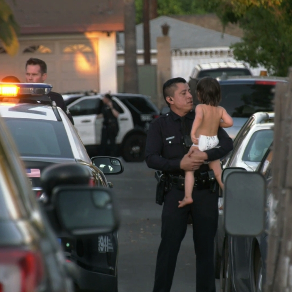 An officer holds a young child who was rescued from a Sun Valley home where a man and woman were found shot dead on Aug. 19, 2019. (Credit: OnScene.TV)