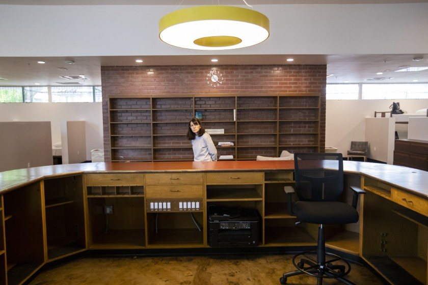 Neighbor Karen Miniotti looks over the Gardner Public Library's original circulation desk, which was restored in the newly repurposed Gardner Library Women's Bridge Shelter in Hollywood, on Sept. 10, 2019. (Credit: Brian van der Brug/Los Angeles Times)