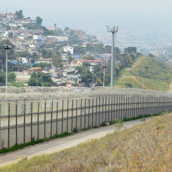 A fence runs along the US-Mexico border between the Otay Mesa and San Ysidro ports of entry in and near San Diego, California, across from Tijuana, Mexico (L). (Credit: FREDERIC J. BROWN/AFP/Getty Images)