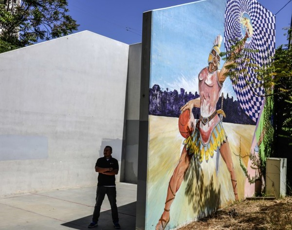 Luis Campos stands on a handball court used by El Centro del Pueblo in Echo Park. City officials were debating during the summer of 2019 whether to build housing for the homeless on that lot.(Credit: Irfan Khan / Los Angeles Times)