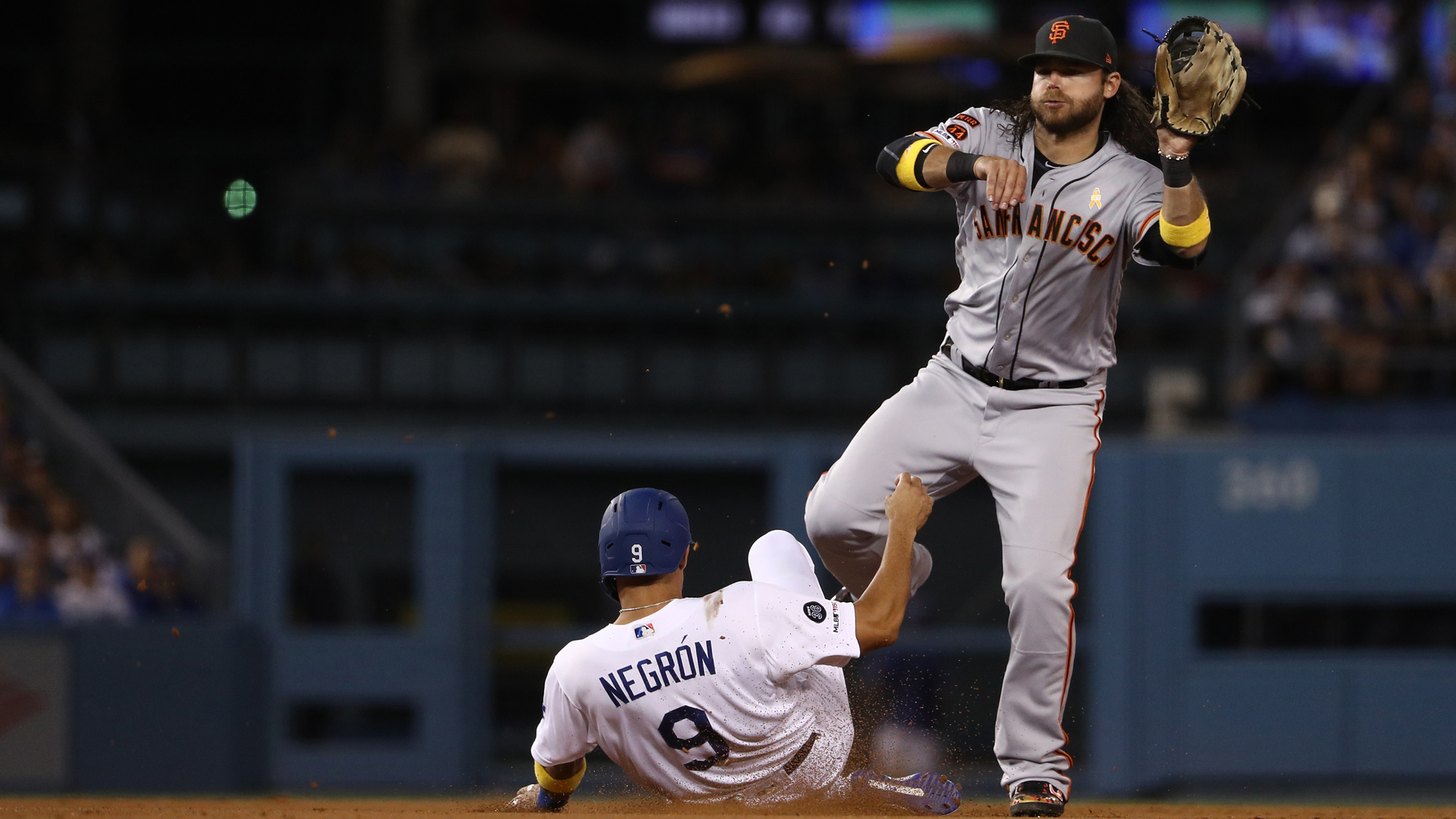 Brandon Crawford #35 of the San Francisco Giants follows through on his throw to first base to turn the double play as Kristopher Negron #9 of the Los Angeles Dodgers slides into second base during the eighth inning of the MLB game at Dodger Stadium on September 07, 2019 in Los Angeles, California. The double play ended the inning. (Credit: Victor Decolongon/Getty Images)