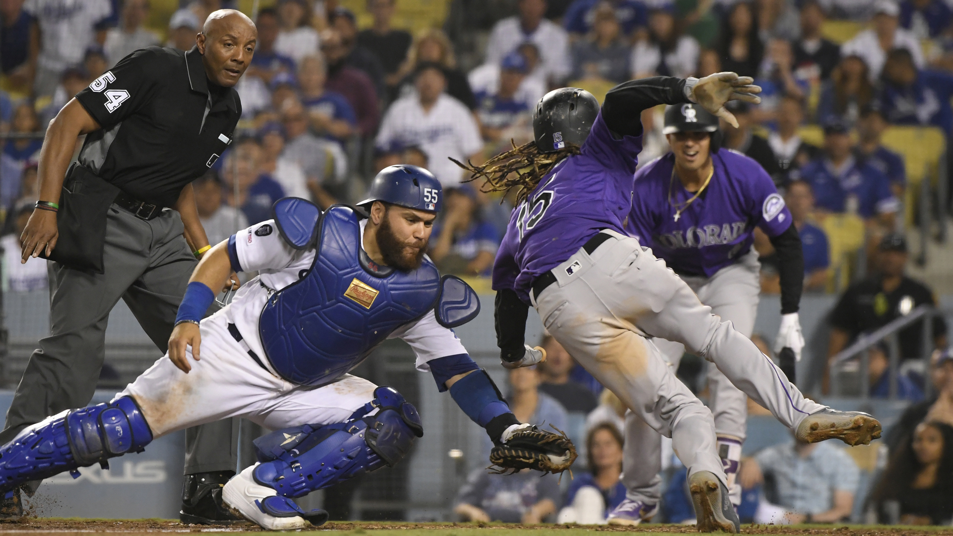 Russell Martin #55 of the Los Angeles Dodgers tags Raimel Tapia #15 of the Colorado Rockies out at the plate on a single by Sam Hilliard #43 as umpire Greg Gibson #53 makes the call in the eighth inning at Dodger Stadium on September 21, 2019 in Los Angeles, California. (Credit: John McCoy/Getty Images)