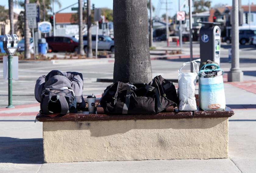 A homeless man sleeps with his belongings packed in bags next to him at the Newport Pier in this undated photo.(Credit: Raul Roa / Los Angeles Times)