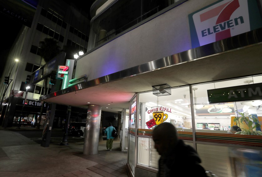 Homeless men mill around outside a 7-Eleven store along Pine Avenue in Long Beach. (Credit: Luis Sinco / Los Angeles Times)